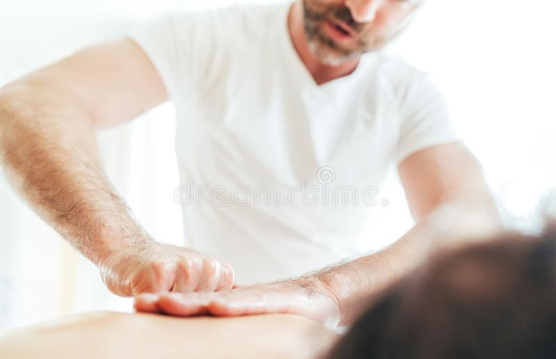 Hombre barbudo del masajista que hace manipulaciones del masaje en la zona del área del omóplato durante el masaje joven del cuer fotografía de archivo