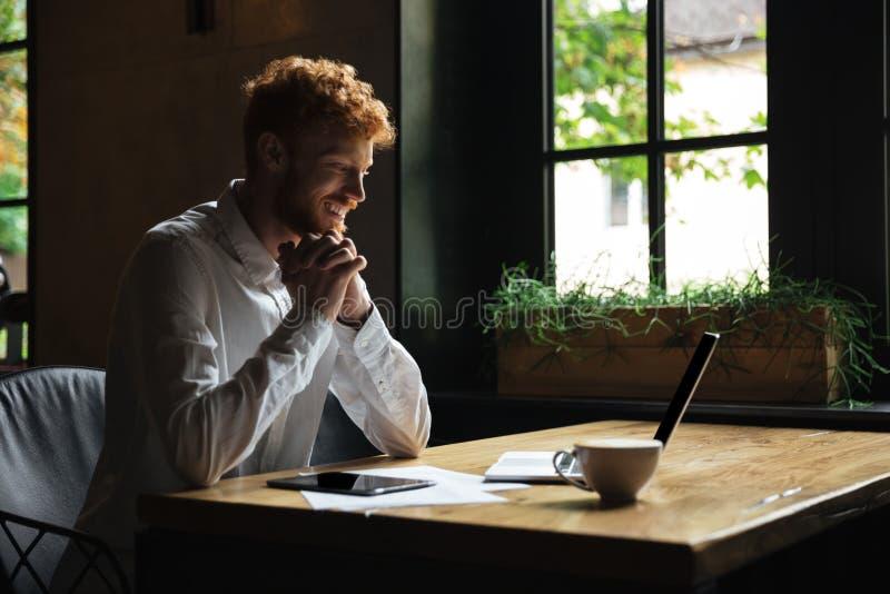 Hombre barbudo del readhead feliz joven que lleva a cabo las manos junto que se sientan imagen de archivo libre de regalías