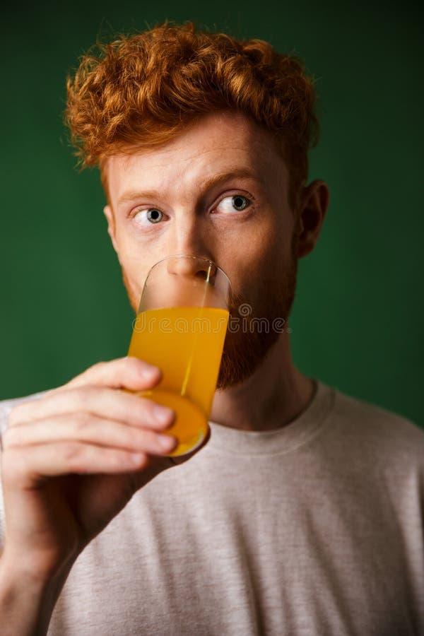 Hombre barbudo del readhead rizado que bebe el zumo de naranja foto de archivo libre de regalías