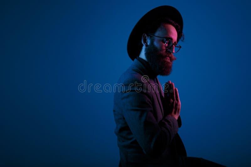 Hombre barbudo del retrato en sombrero y traje, con los ojos cerrados y las lentes, guardando las palmas juntas, en fondo azul ma imagenes de archivo