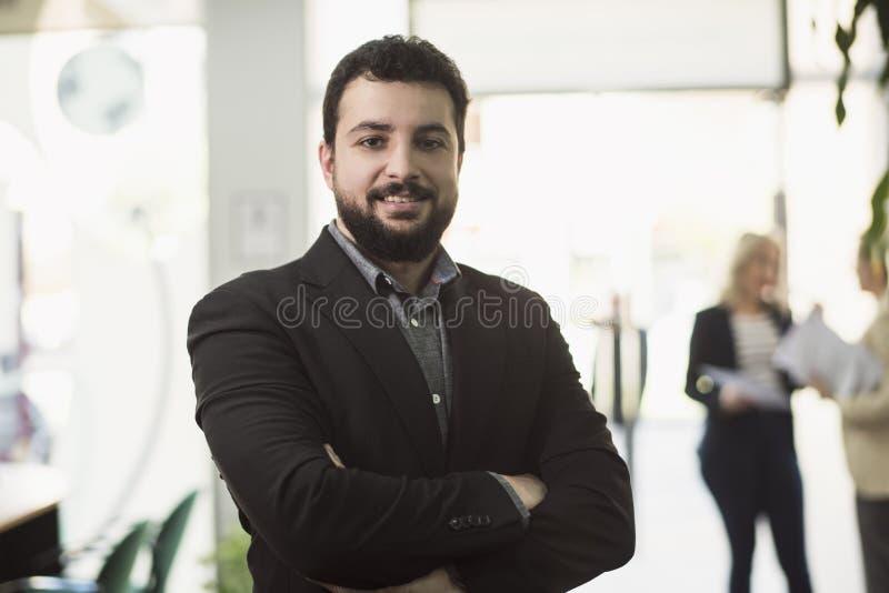 Hombre barbudo del traje que presenta en lugar de trabajo de la oficina foto de archivo