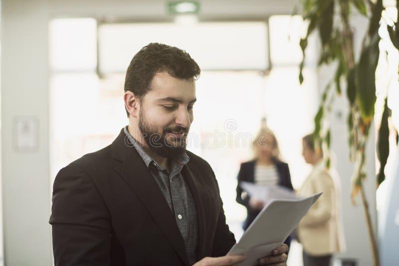 Hombre barbudo del traje que presenta en lugar de trabajo de la oficina foto de archivo libre de regalías