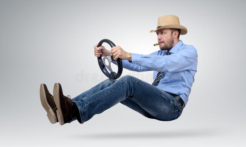 Hombre barbudo divertido en un coche del conductor del sombrero y del cigarro con una rueda imagen de archivo
