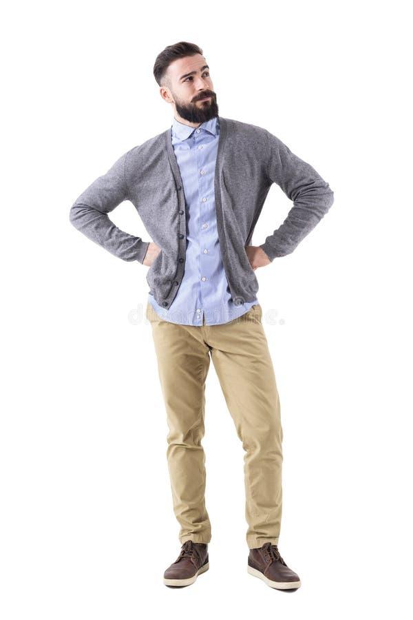 Hombre barbudo elegante hermoso que piensa y que mira para arriba con los brazos en caderas foto de archivo