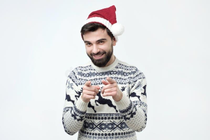 Hombre barbudo emocionado en casquillo rojo de la Navidad que señala los fingeres en la cámara imágenes de archivo libres de regalías