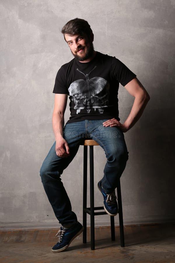 Hombre barbudo en camiseta negra con sentarse en un taburete de bar gris imágenes de archivo libres de regalías