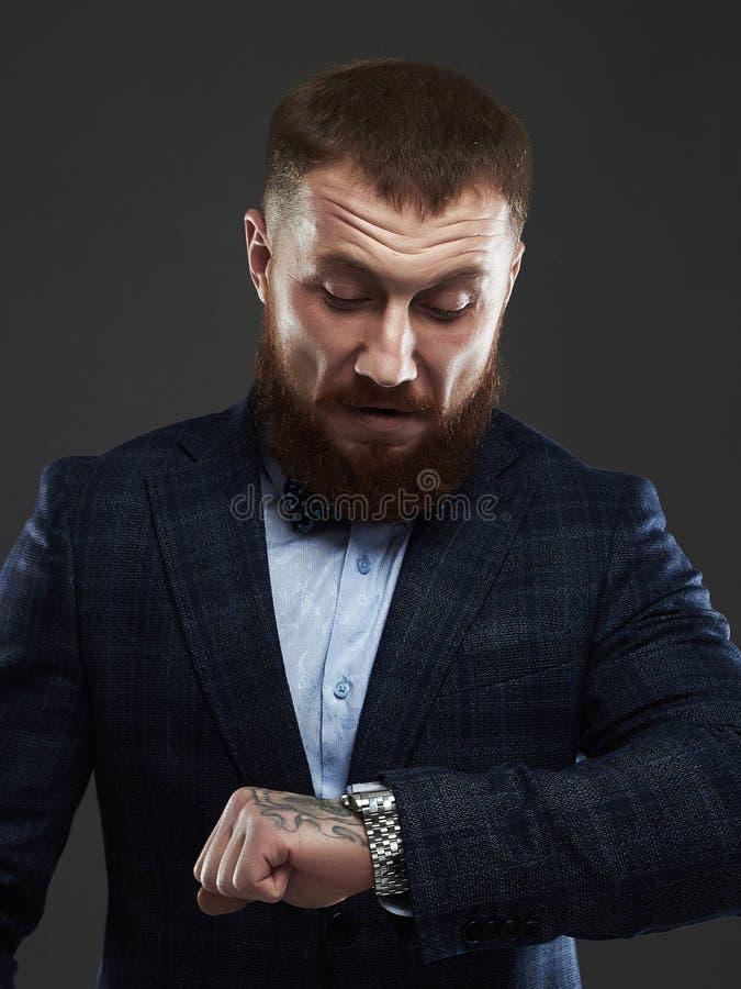 Hombre barbudo en el traje que espera y que mira el reloj imagenes de archivo