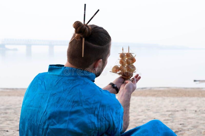 Hombre barbudo en kimono azul con el modelo de nave de la tenencia del bollo del pelo con las conchas marinas delante del río imagenes de archivo