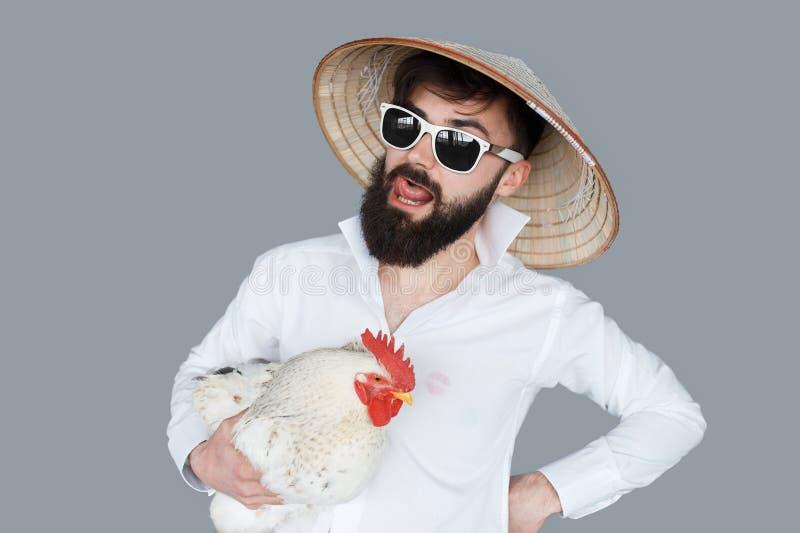Hombre barbudo en la camisa blanca que sostiene un pollo foto de archivo libre de regalías
