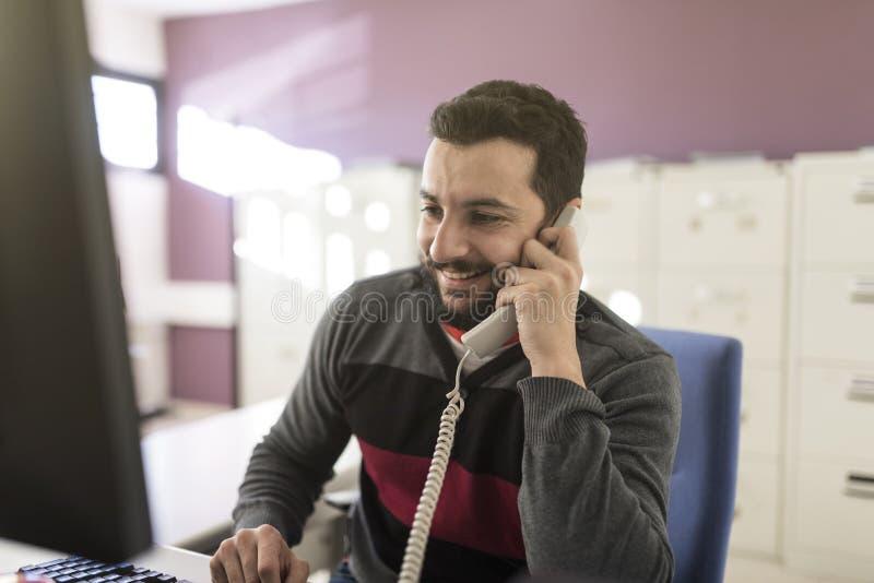 Hombre barbudo en oficina en el teléfono con hablar ligero ambiente fotos de archivo libres de regalías