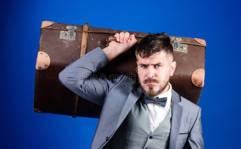 Hombre barbudo en traje esthete elegante con el bolso del vintage Viaje de negocios con la maleta retra Bolso pesado viajero madu imagenes de archivo