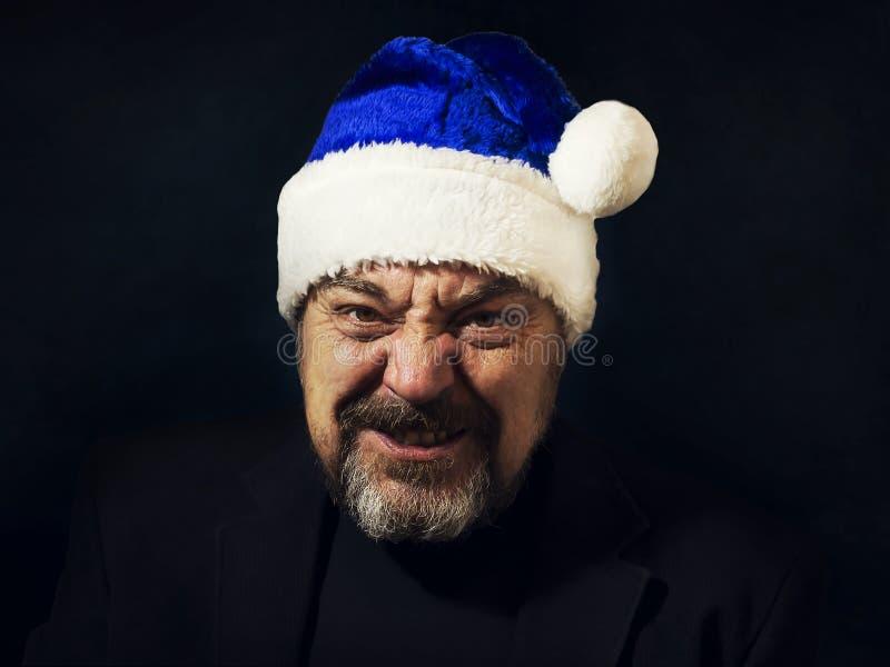 Hombre barbudo en un sombrero de Santa Claus en un fondo oscuro Año Nuevo Navidad Enhorabuena fotos de archivo