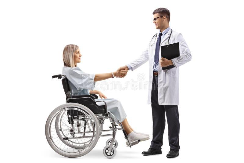 Hombre barbudo en una silla de ruedas que sacude las manos con una mujer joven imagenes de archivo
