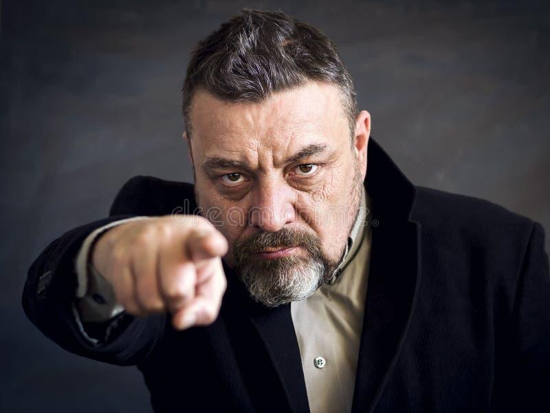 Hombre barbudo enojado en un punto negro del traje un finger en usted Copie el espacio Un gesto de la opción imagen de archivo libre de regalías