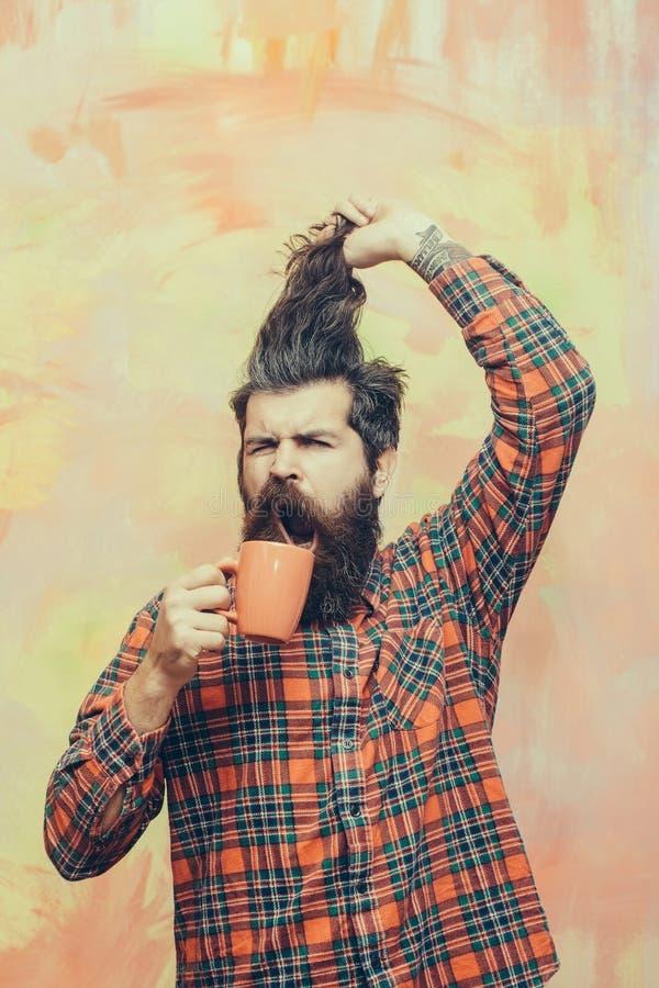 Hombre barbudo enojado que sostiene el pelo de la franja y la taza anaranjada foto de archivo libre de regalías