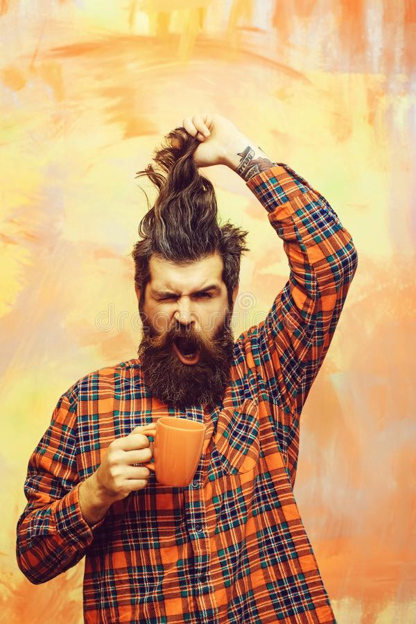 Hombre barbudo enojado que sostiene el pelo de la franja y la taza anaranjada imagenes de archivo