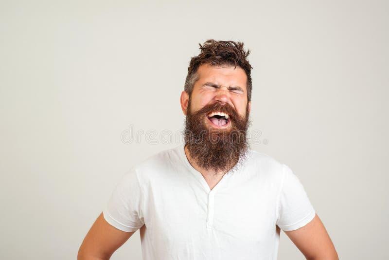 Hombre barbudo feliz elegante con los ojos cerrados que grita en el fondo blanco El varón excitó la expresión de la cara E imagen de archivo libre de regalías