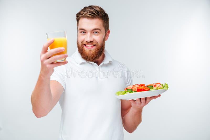 Hombre barbudo feliz que come el bocado sano con las verduras fotos de archivo libres de regalías
