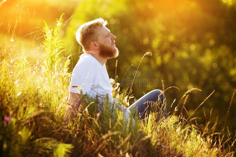 Hombre barbudo feliz que descansa entre wildflowers imagenes de archivo