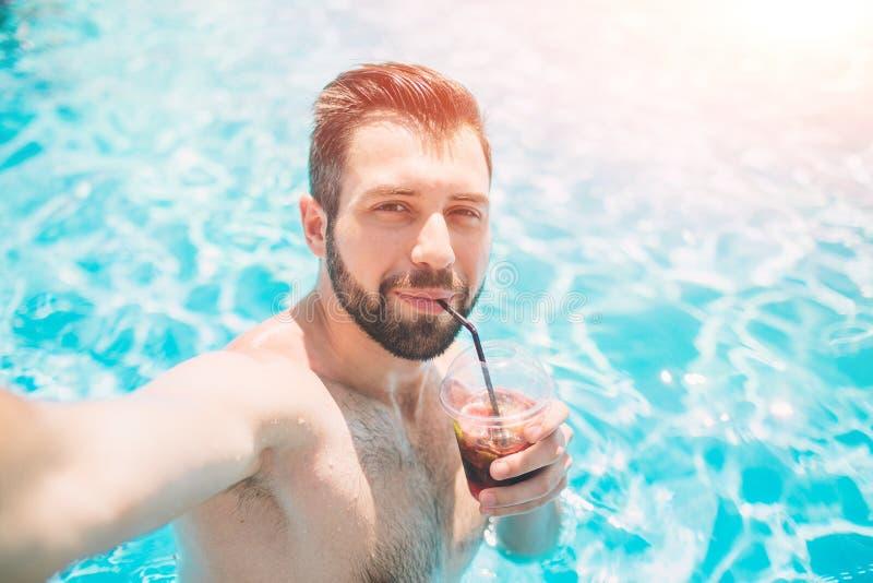 Hombre barbudo feliz que hace el selfie en piscina Él está bebiendo un cóctel y se está relajando fotografía de archivo