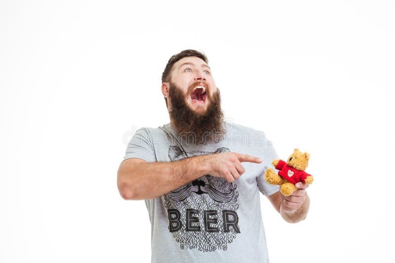 Hombre barbudo feliz que lleva a cabo el pequeño oso y la risa de peluche foto de archivo libre de regalías