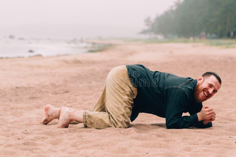 Hombre barbudo feliz que se arrastra en todos los fours la playa imagen de archivo libre de regalías