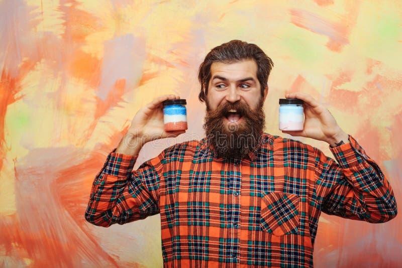 Hombre barbudo feliz que sostiene dos tarros cosméticos imagenes de archivo