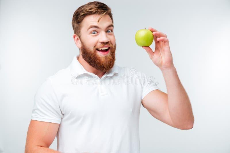 Hombre barbudo feliz que sostiene la manzana verde y que mira la cámara fotos de archivo