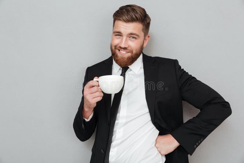 Hombre barbudo fresco sonriente en el traje que sostiene la taza de café fotos de archivo