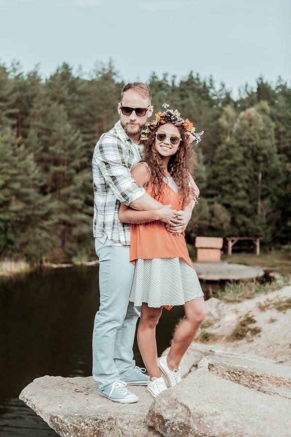 Hombre barbudo fuerte que abraza a su novia oscuro-cabelluda rizada hermosa feliz imagenes de archivo