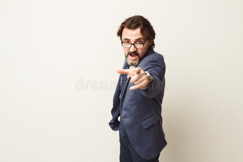 Hombre barbudo furioso que grita ruidosamente, punto en la cámara fotografía de archivo libre de regalías
