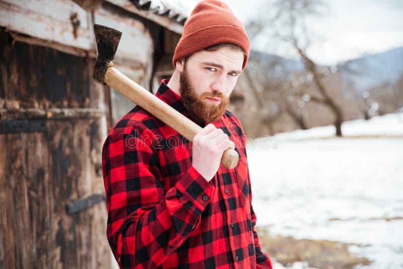 Hombre barbudo hermoso con el hacha en pueblo imagen de archivo