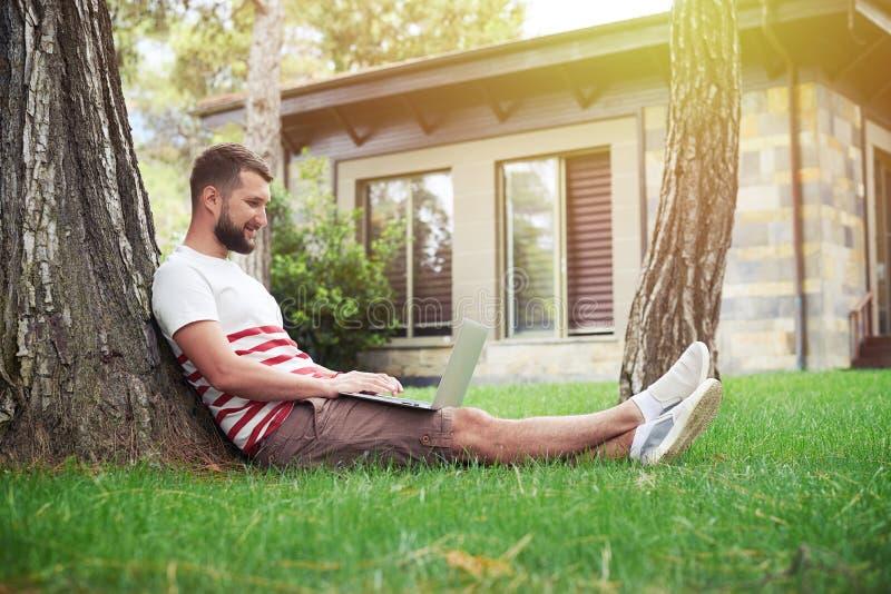 Hombre barbudo hermoso con el ordenador portátil en patio trasero debajo del árbol fotografía de archivo