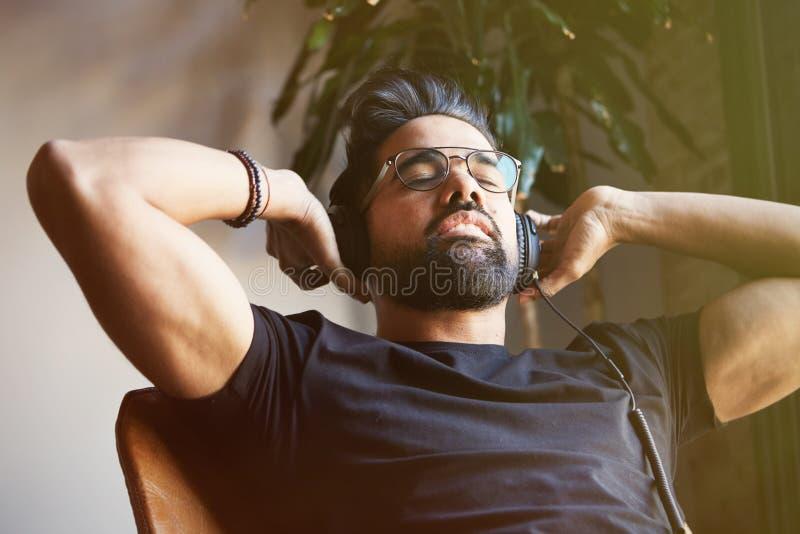 Hombre barbudo hermoso en auriculares que escucha la música en casa Concepto del tiempo de la relajación y de resto Fondo enmasca fotos de archivo libres de regalías