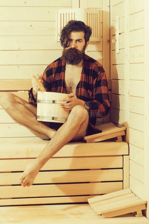 Hombre barbudo hermoso en baño de madera con el cubo fotografía de archivo