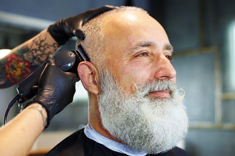 Hombre barbudo hermoso en barbería profesional fotografía de archivo