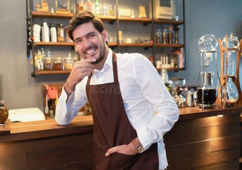 Hombre barbudo hermoso en el delantal que mira la cámara y que lleva a cabo la mano en la barbilla mientras que se coloca en el c fotografía de archivo