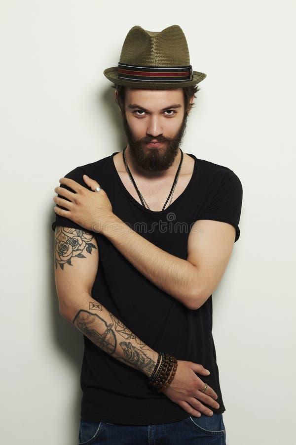 Hombre barbudo hermoso en sombrero Muchacho brutal con el tatuaje fotografía de archivo