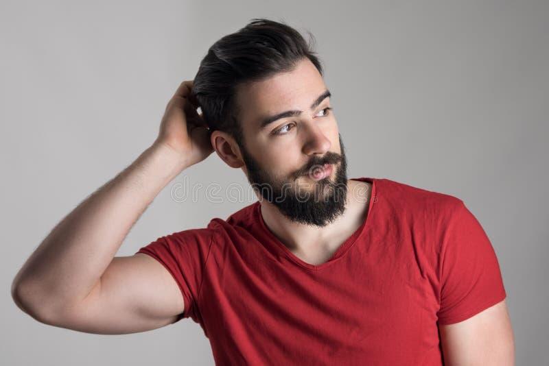 Hombre barbudo hermoso joven en la camiseta roja que rasguña la cabeza que mira lejos foto de archivo libre de regalías