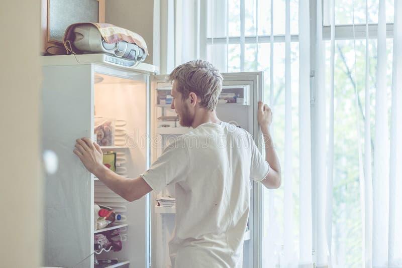 Hombre barbudo hermoso joven que se coloca cerca de cocina opended del refrigerador en casa imagen de archivo libre de regalías