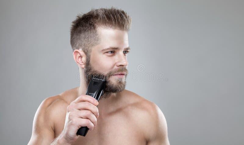 Hombre barbudo hermoso que arregla su barba con un condensador de ajuste fotos de archivo