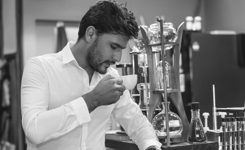 Hombre barbudo hermoso que bebe una taza de café en el café Tono blanco y negro fotos de archivo libres de regalías