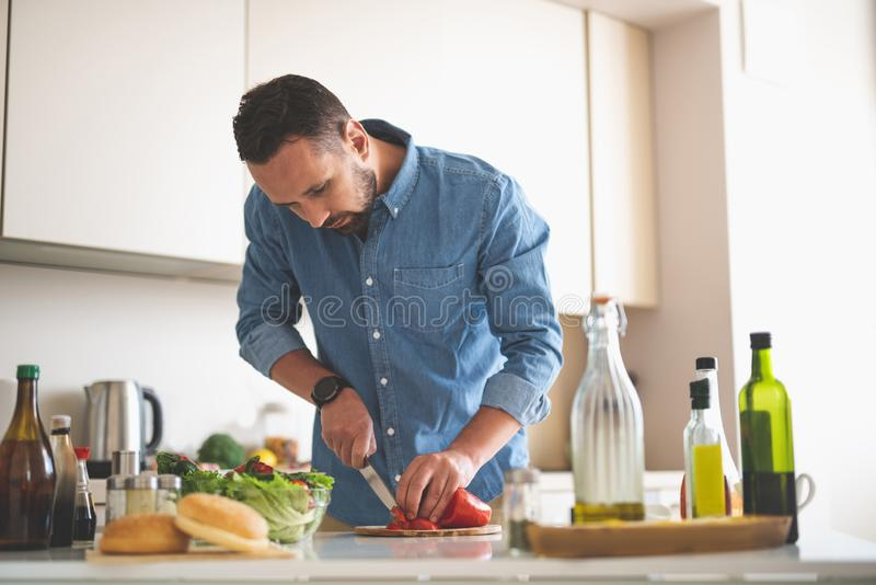 Hombre barbudo hermoso que cocina la cena en la cocina foto de archivo