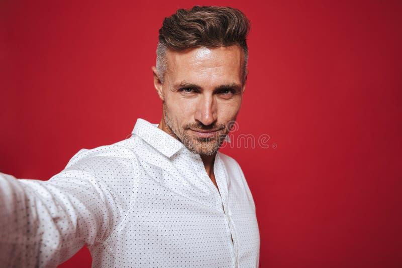 Hombre barbudo hermoso 30s en la camisa blanca que sonríe y que toma selfi foto de archivo libre de regalías