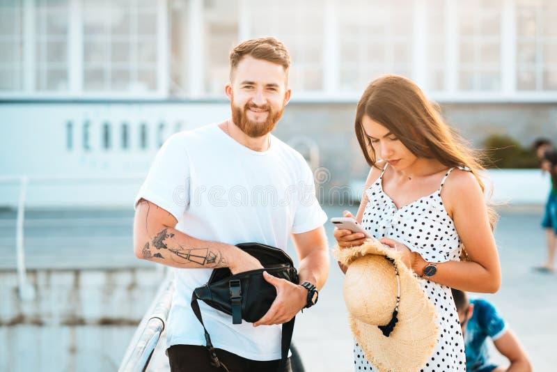 Hombre barbudo hermoso y su muchacha hermosa que presentan en la cámara foto de archivo