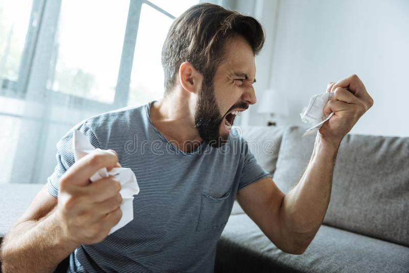 Hombre barbudo infeliz que tiene un ataque de nervios fotografía de archivo