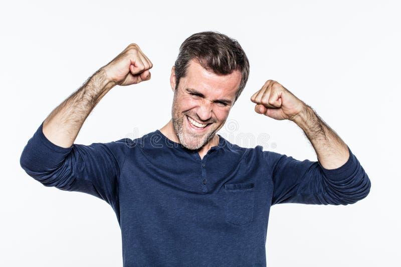 Hombre barbudo joven alegre que sonríe y que ríe con los puños para arriba fotografía de archivo libre de regalías