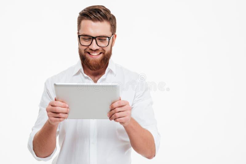 Hombre barbudo joven alegre que usa la tableta imagenes de archivo