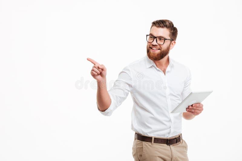 Hombre barbudo joven alegre que usa la tableta imágenes de archivo libres de regalías