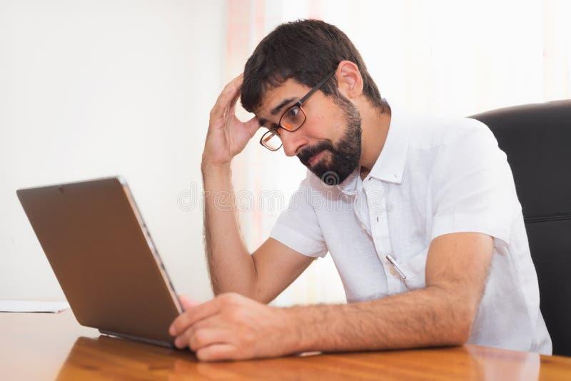 Hombre barbudo joven de la expresión preocupante que trabaja en la oficina fotos de archivo libres de regalías